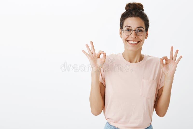 Optymistycznie i wzmacniający potomstwa ustalali szczęśliwego żeńskiego coworker w round koszulki i szkieł seansu ok gescie i obrazy stock