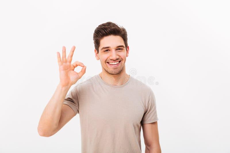 Optymistycznie mężczyzna ma szczecina i brown włosy pokazuje ok znaka dalej fotografia royalty free