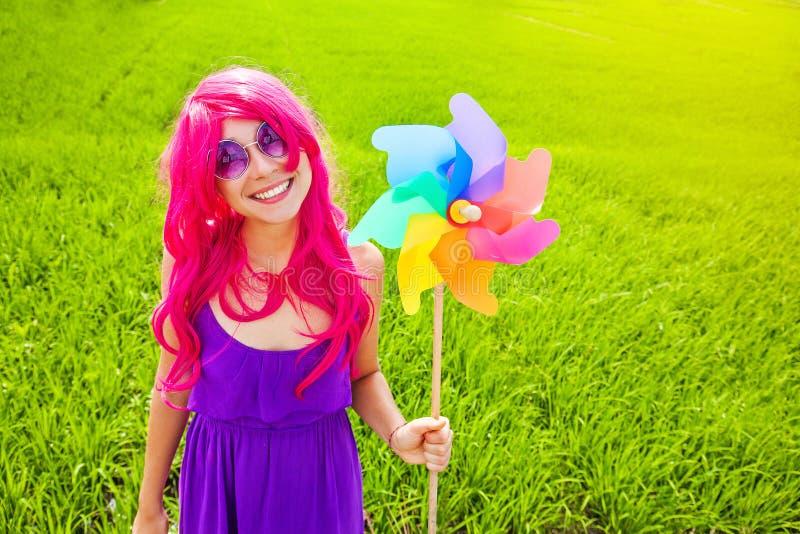 Optymistycznie młoda kobieta jest ubranym różową perukę obrazy stock