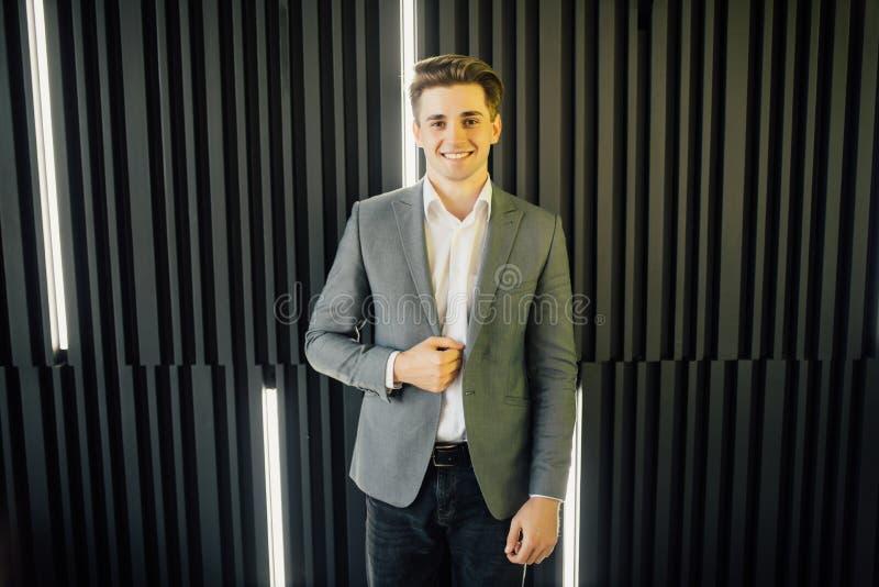 Optymistycznie portret przystojna młoda biznesmen pozycja przeciw ciemnej drewnianej ścianie obraz royalty free