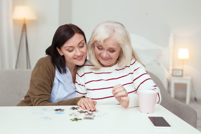 Optymistycznie starsza osoba opiekunu i kobiety gromadzić łamigłówka obrazy stock