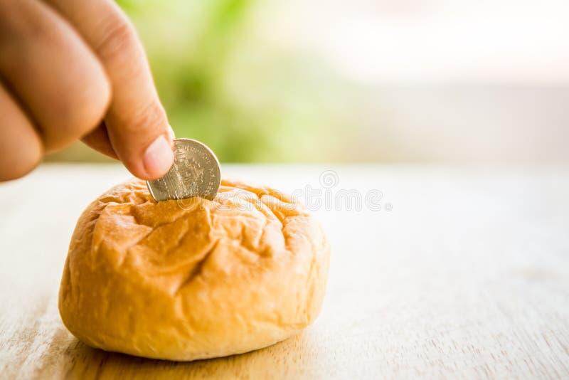 Opuszczać monety w chlebowym banku zdjęcia stock