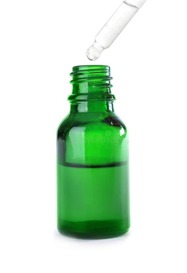 Opuszczający ziołowego istotnego olej w butelkę odizolowywającą zdjęcie royalty free