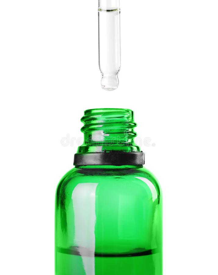 Opuszczający ziołowego istotnego olej w butelkę odizolowywającą obraz royalty free