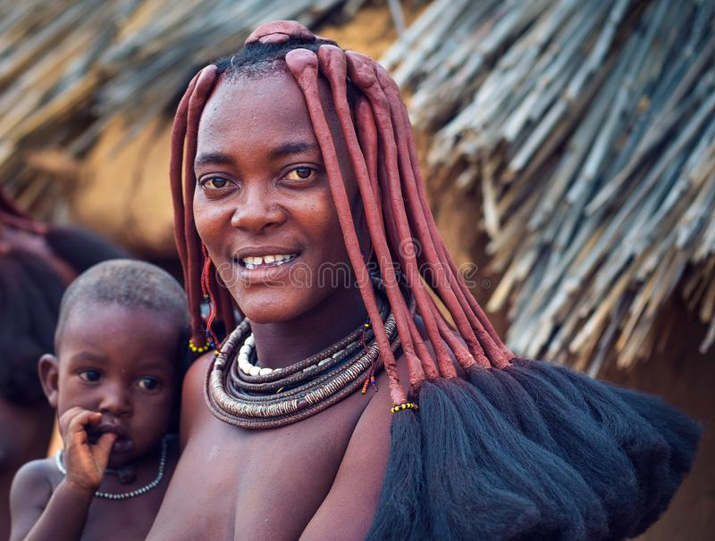 Portrait of a young himba woman with her child wearing traditional hairstyle stock photo