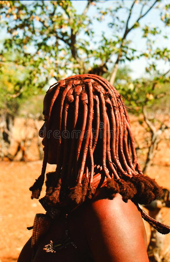 OPUWO, NORTH NAMIBIA - MAY 8. 2013: Close up of Himba woman with trees background stock images