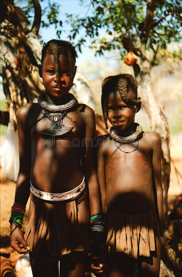 OPUWO, NORTH NAMIBIA - MAY 8. 2013: Close up of two Himba boys with trees background stock photography