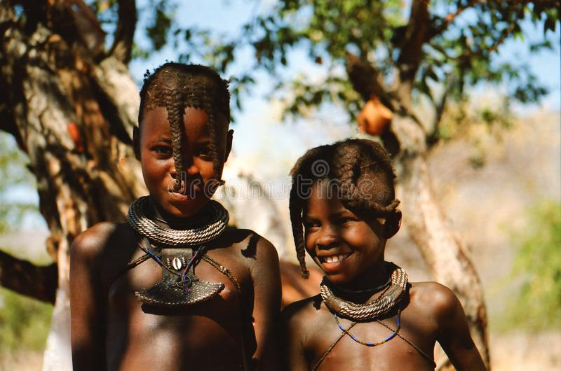 OPUWO, NORTH NAMIBIA - MAY 8. 2013: Close up of two Himba boys with trees background royalty free stock photos