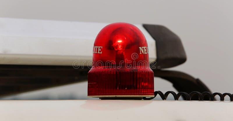 opvlammend rood noodsituatielicht dat op wit geïsoleerd is stock afbeelding
