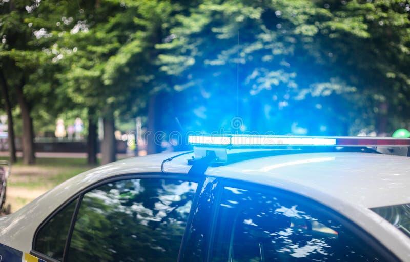 Opvlammende lichten van de politiewagen tegen stads groen park royalty-vrije stock fotografie