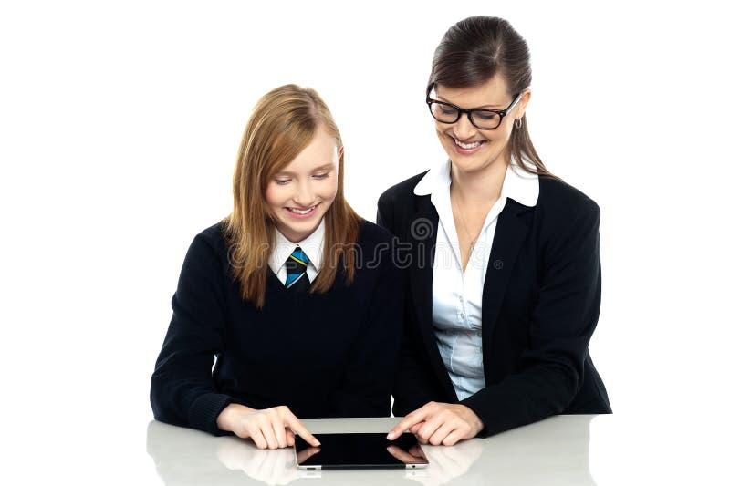 Opvoeder en student die een tabletapparaat onderzoeken royalty-vrije stock afbeelding