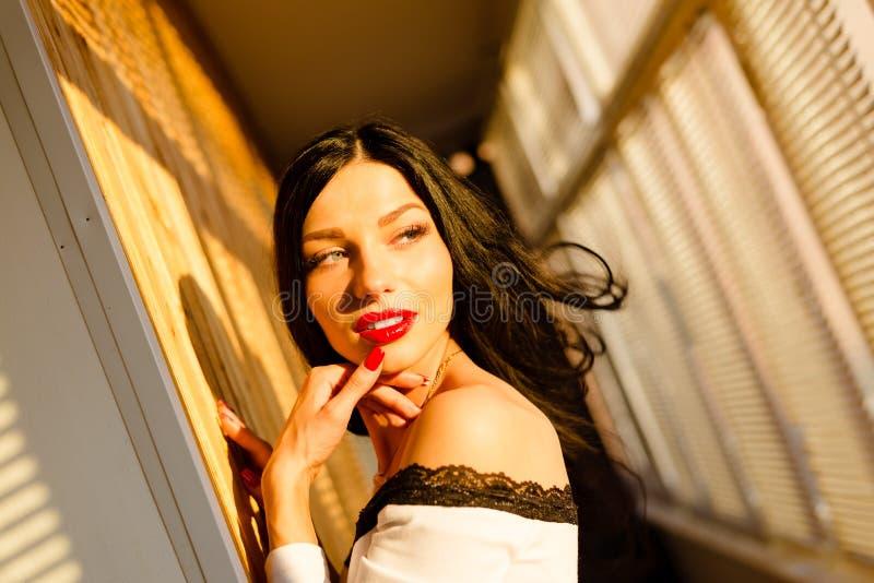 Opwekkend jonge dame met rode binnen lippen op balkon royalty-vrije stock fotografie