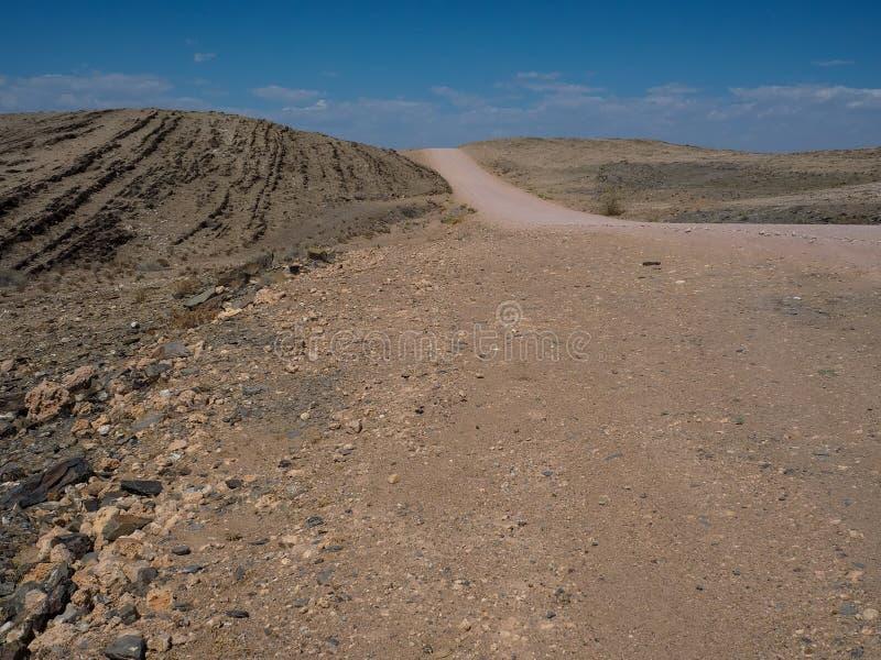 Opyspace του οδικού ταξιδιού μέσω του ξηρού σκονισμένου εδάφους τοπίων βουνών βράχου της ερήμου Namib με το διαχωρισμό της πέτρας στοκ εικόνες