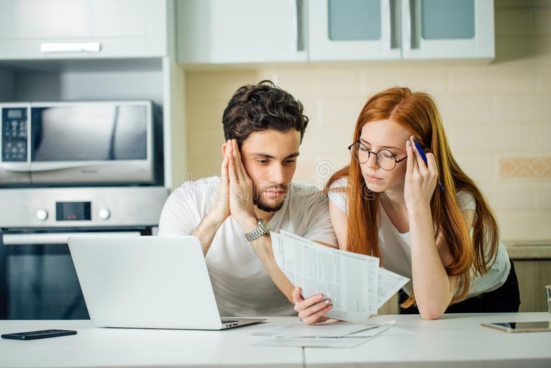 Orçamento de controlo da família, revendo suas contas bancárias usando o portátil na cozinha imagem de stock