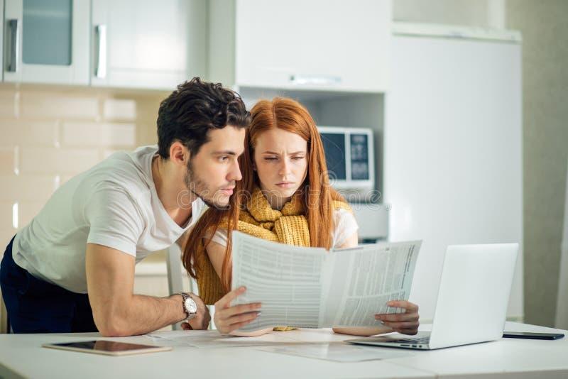 Orçamento de controlo da família, revendo suas contas bancárias usando o portátil na cozinha foto de stock royalty free