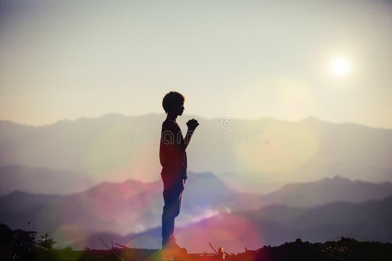 A oração espiritual cede o brilho do sol com fundo bonito borrado do por do sol foto de stock