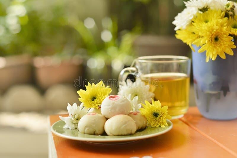 Ora del the con pasticceria cinese e tè e fiore su una sedia arancio immagini stock libere da diritti