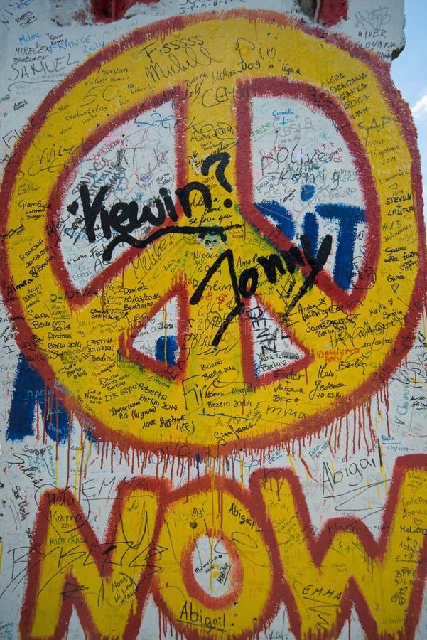 Ora segno dei graffiti di pace sul muro di Berlino immagini stock