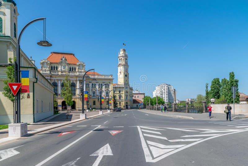 ORADEA RUMÄNIEN - 28 APRIL, 2018: Folk som går på gatan med det Oradea stadshuset i bakgrund arkivfoton