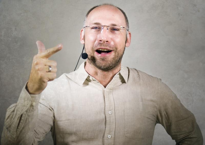 Orador atrativo e seguro feliz do homem de negócios com os auriculares que dão o treinamento de treinamento da conferência para o imagens de stock royalty free