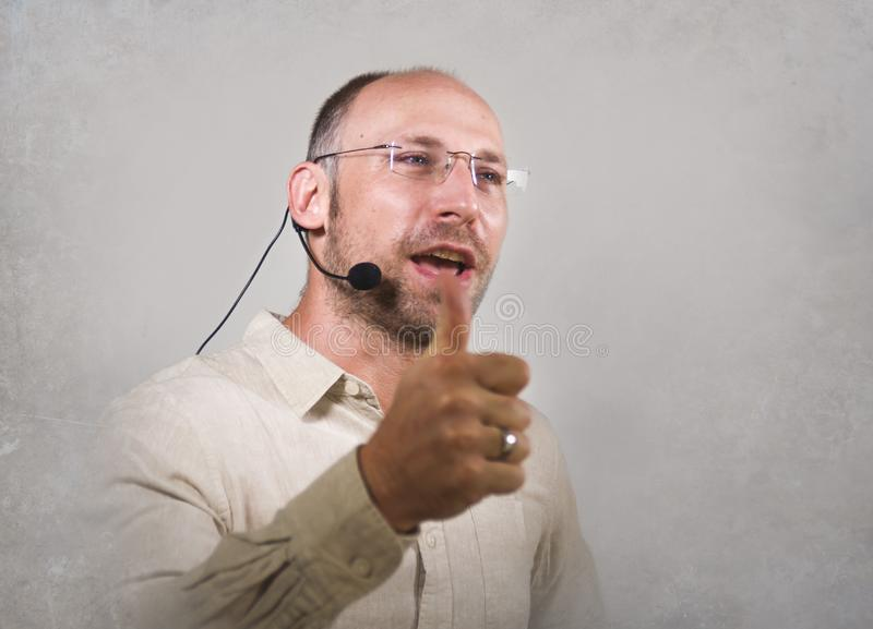 Orador atrativo e seguro feliz do homem de negócios com os auriculares que dão o treinamento de treinamento da conferência para o fotografia de stock