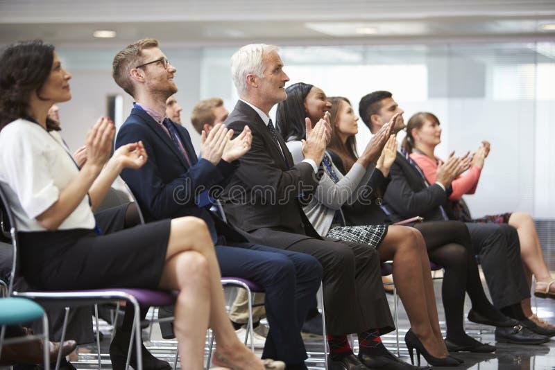Orador de aplauso da audiência após a apresentação da conferência imagens de stock