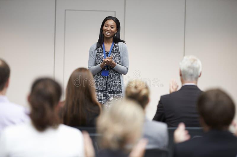 Orador de aplauso da audiência após a apresentação da conferência imagem de stock