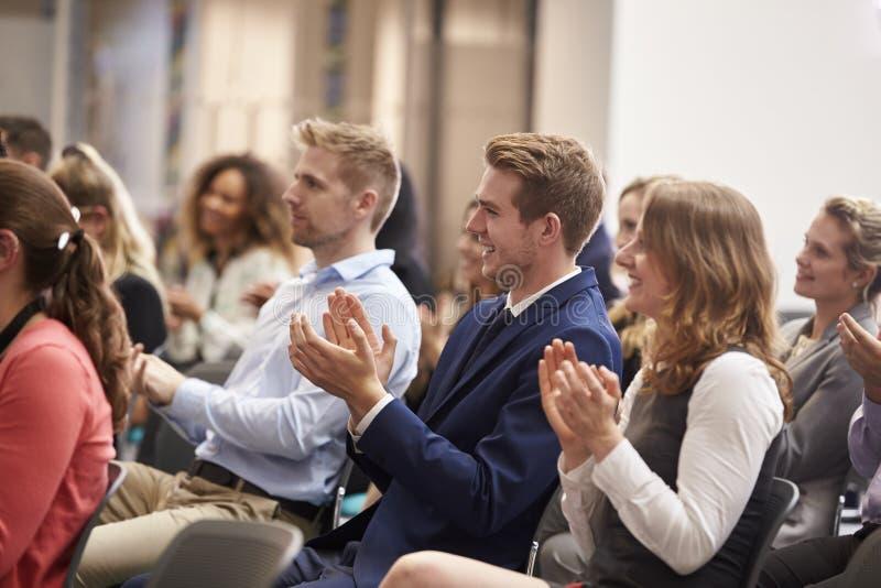 Orador de aplauso da audiência após a apresentação da conferência fotos de stock