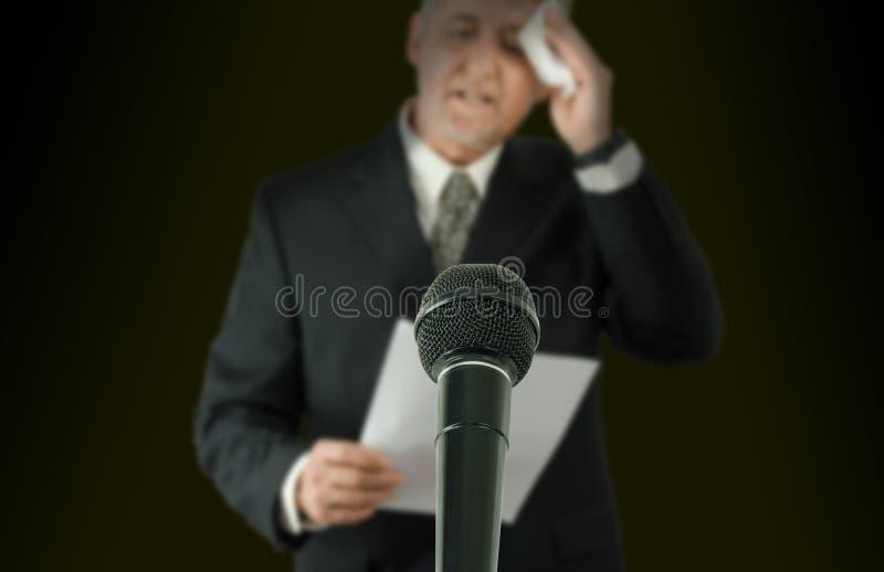 Orador o político nervioso que limpia el micrófono de la frente en f fotos de archivo libres de regalías