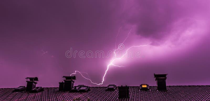 Orage pendant la nuit : Foudre au-dessus d'un toit d'un b?timent photo stock