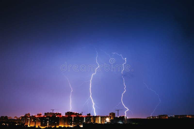 Orages ciel bleu et foudres vifs au-dessus de ville de nuit images stock