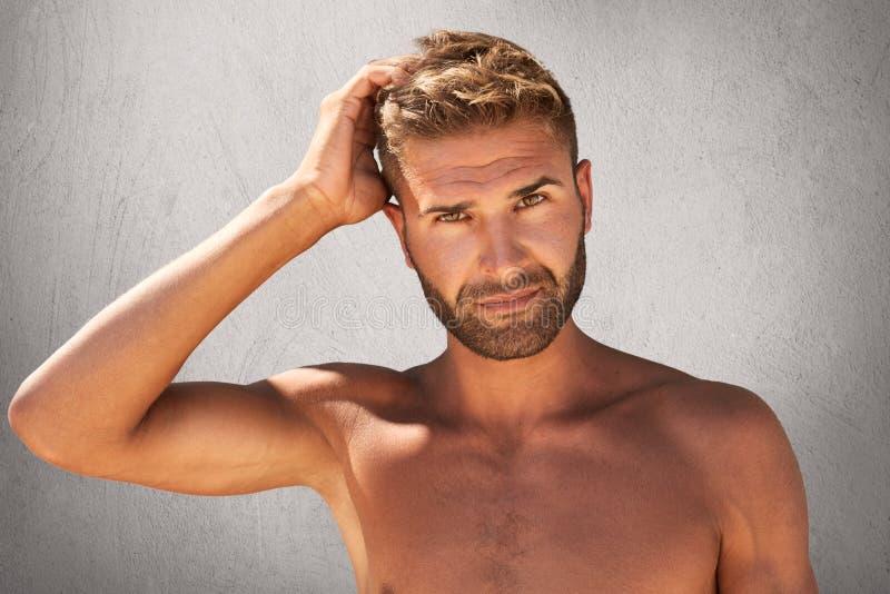Orakad naken idrottsman med mörka ögon och stilfull frisyr som skrapar hans huvud, över grå bakgrund Muskulösa unga han fotografering för bildbyråer