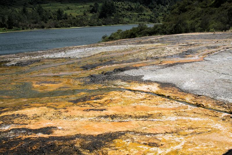 Orakei Korako hidden geothermal valley - Emerald terrace: Close up of colorful rainbow sinter terrace. Covered with stripes of yellow and white microbial mats royalty free stock photo