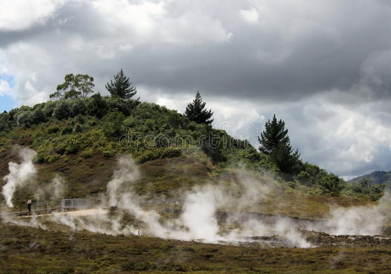 Orakei Korako hidden geothermal valley: View on steaming hills Fumaroles. Under clouded sky royalty free stock image