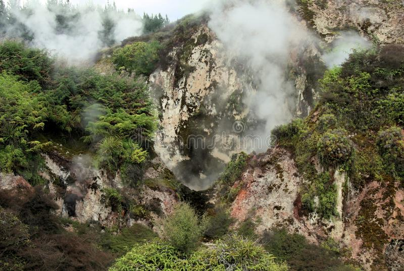 Orakei Korako hidden geothermal valley: View on steaming rocks Fumaroles. At mountain face stock photo