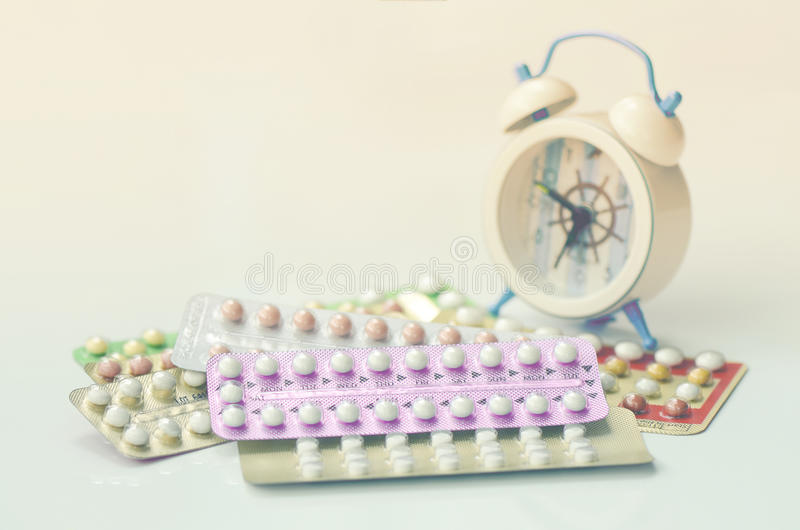 Oral contraceptive pills with alarm clock background. royalty free stock image