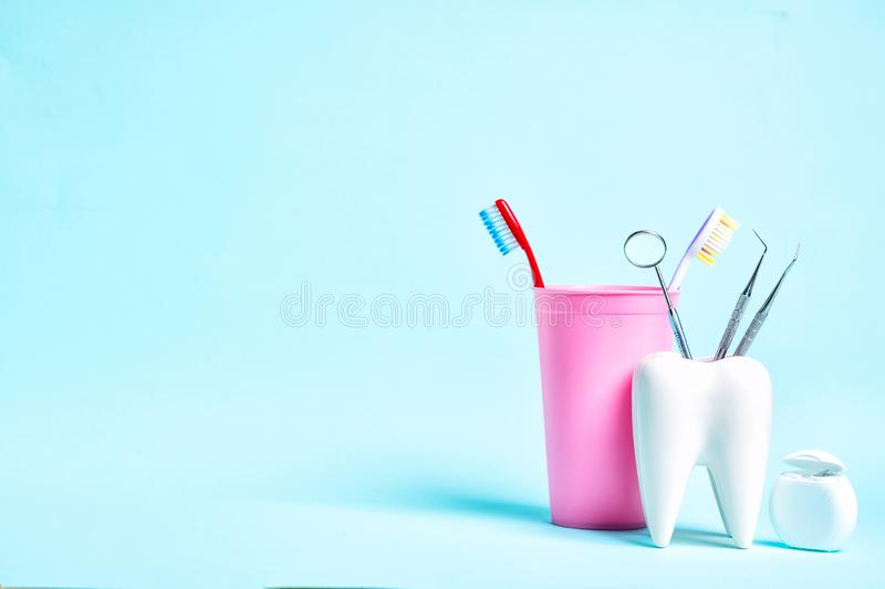 Oral dental hygiene. Dental health and teethcare concept. Dental mirror with explorer probes in healthy white tooth model near. Dental floss and toothbrushes in stock images