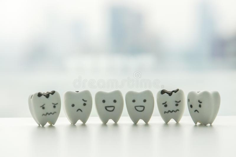 Oral health icon - isolated healthy teeth and decayed teeth cartoon with smiley and sad face. Human oral health icon - isolated healthy teeth and decayed teeth royalty free stock photo