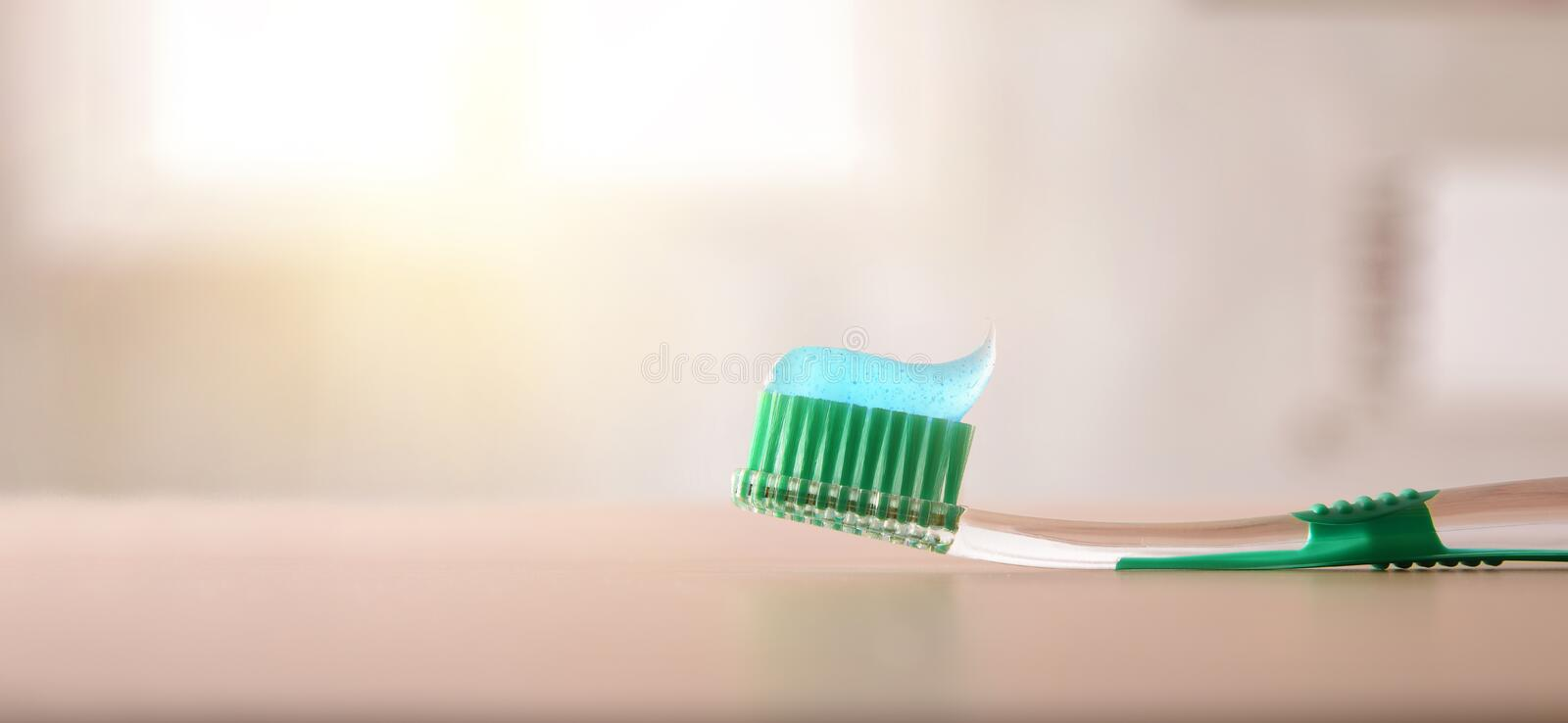 Oral hygiene with toothbrush with toothpaste on table in bathroom. Concept oral hygiene with toothbrush on wood table in bathroom. Horizontal composition. Front stock images