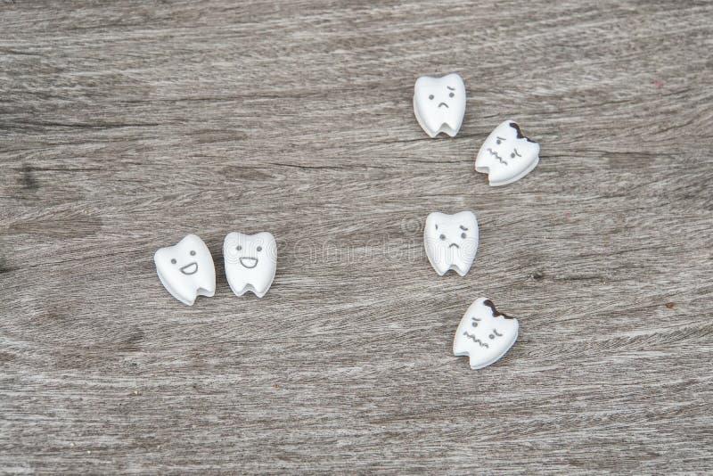 Oralna zdrowie ikona - śliczny zdrowy i płacz gniliśmy zęby na drewnie zdjęcia stock