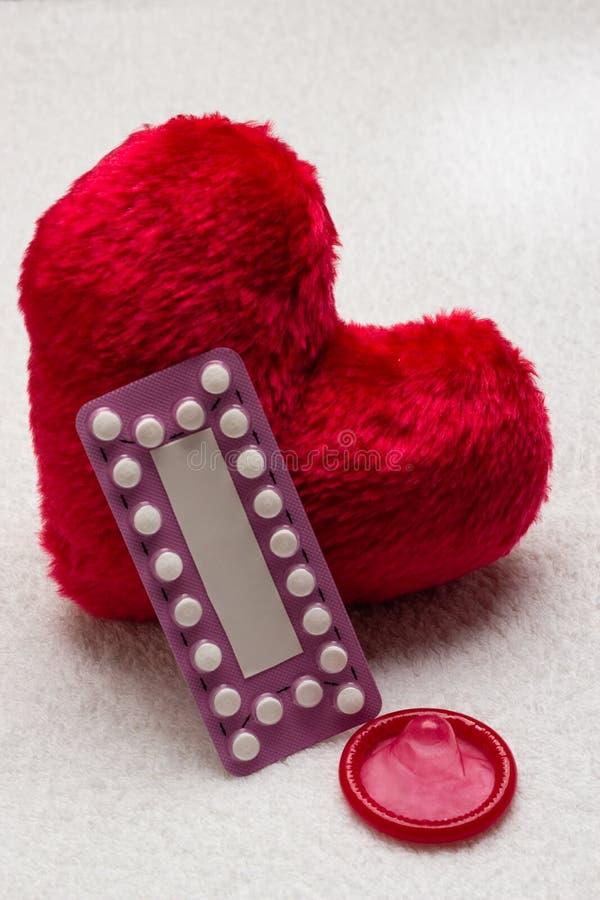 Oralny antykoncepcyjnych pigułek kondom na czerwonym sercu fotografia royalty free