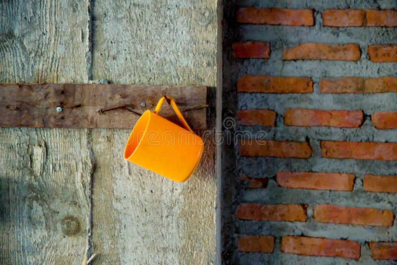 Orance hänger den pastic koppen på grungeväggen vid spikar avbilda för bacakground, tapet, printing, artikel och kopieringsutrymm arkivbild