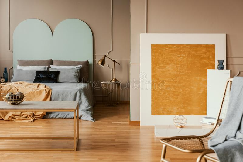 Orange abstract painting in stylish bedroom with blue sheets stock images