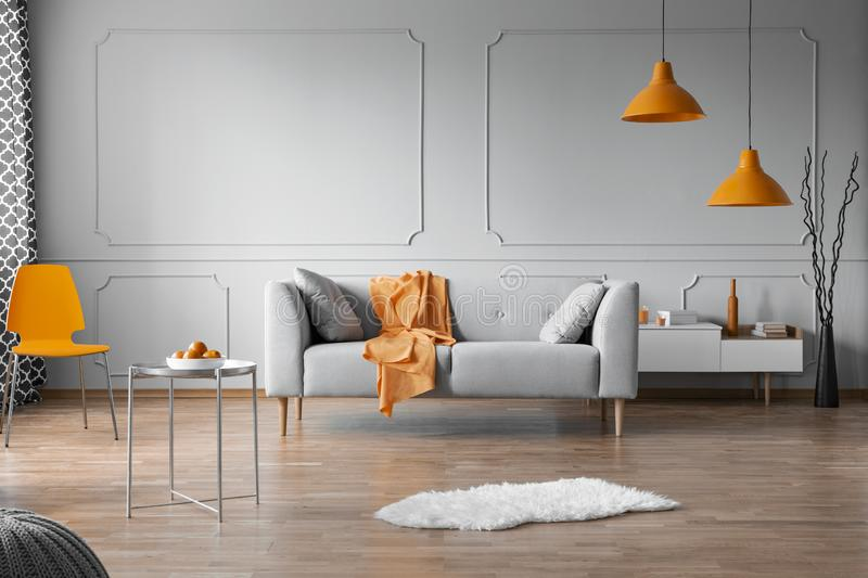 Orange accents in grey living room interior with copy space on empty wall royalty free stock photo
