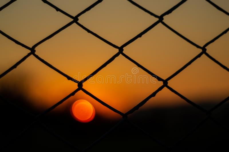 Orange aftonhimmel med den suddiga solen på horisonthostaketet Idérik idé underexponerat foto arkivbilder