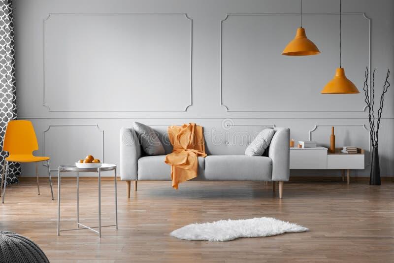 Orange Akzente im grauen Wohnzimmer Innen mit Kopienraum auf leerer Wand lizenzfreies stockfoto