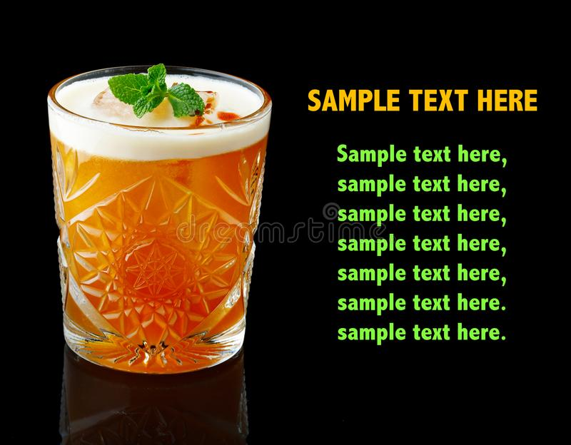 Orange alcohol cocktail with fresh mint isolated on black royalty free stock photography