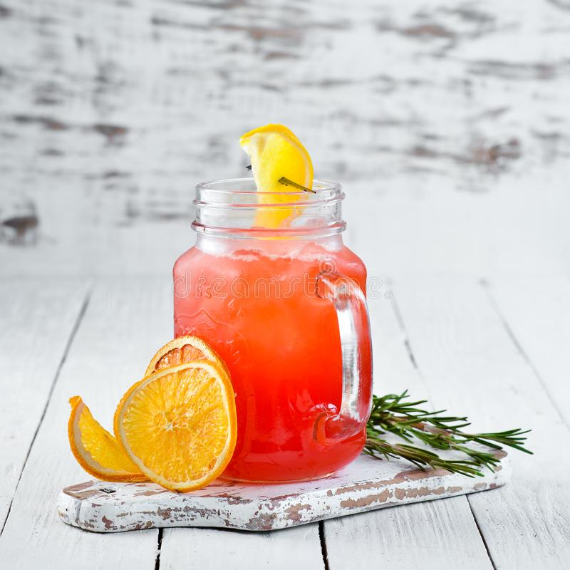 Orange alcoholic cocktail. Orange juice, rum, grenadine, orange. On a wooden background. Top view. Free copy space stock image