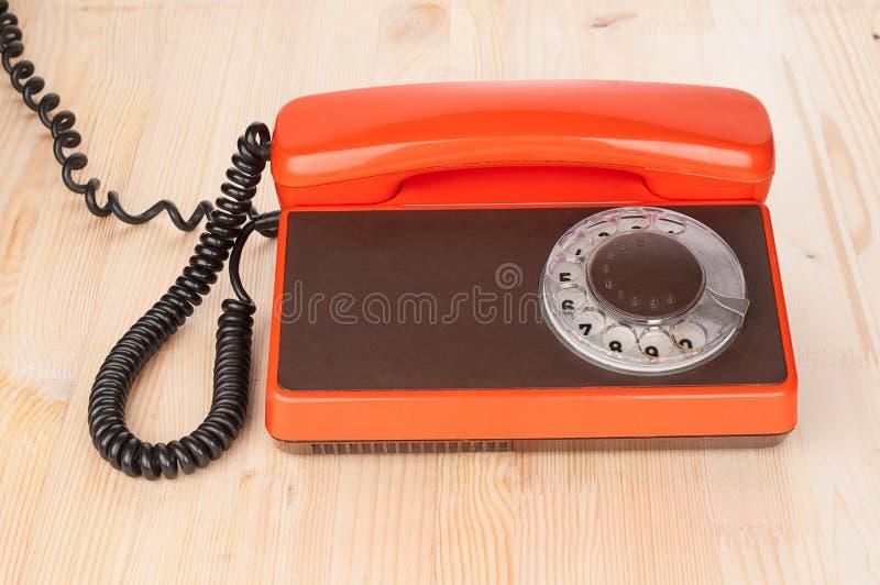 Orange antikes Telefon auf hölzernem Schreibtisch lizenzfreie stockfotos