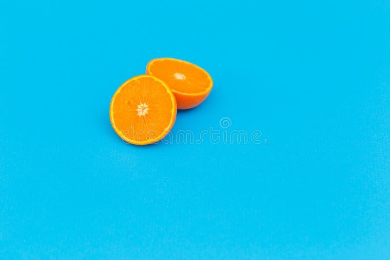 Orange auf einem blauen Hintergrund in einem Schnitt reife Frucht auf einem farbigen Hintergrund stockbild